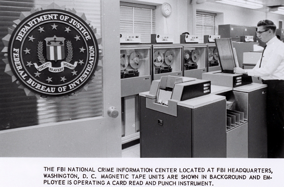 FBI NCIC magnetic tape units are in background; employee is operating a card and punch instrument