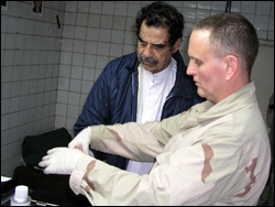 An FBI agent fingerprints Saddam shortly after his capture.