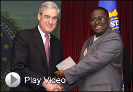 Director Mueller Presenting Award to Minnesota Civic Leader with Play Video Button