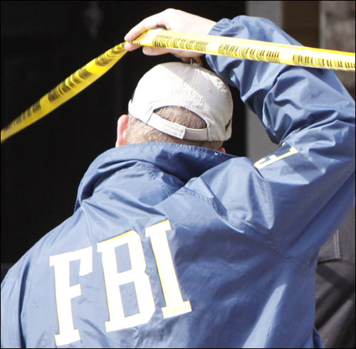 An FBI agent outside the apartment of Najibullah Zazi in Aurora, Colorado. AP Photo