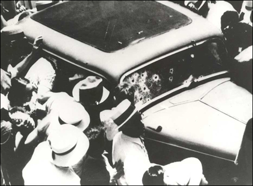 A crowd gathers around Bonnie and Clyde's bullet-ridden sedan not long after the fatal ambush.