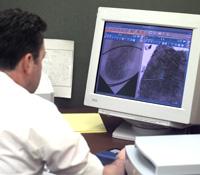 Fingerprint analyst in front of computer