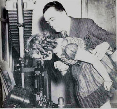 A historical photo of Director J. Edgar Hoover showing actress Shirley Temple a comparison microscope in the Laboratory