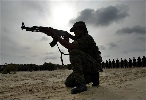 A woman fighter of the Tamil Tigers takes a shooting position in Sri Lanka in July 2007. AP Photo.