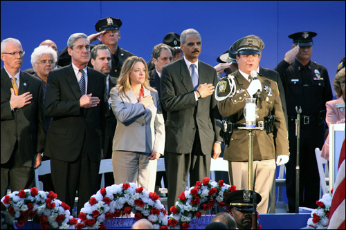 Along with Jennifer Thacker, national president of Concerns of Police Survivors (COPS), U.S. Attorney General Eric Holder (right) and FBI Director Robert Mueller (left) recite the Pledge of Allegiance during the 21st annual Candlelight Vigil for slain officers held May 13, 2009, at the National Law Enforcement Officers Memorial.
