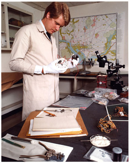 A historical photo of an Explosives Unit examiner analyzing bomb components