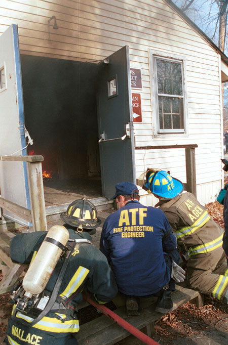 Photograph of three firemen observing a building in flames.