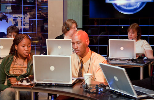 Antonio Jones (center), an FBI intelligence analyst, on the set of America's Most Wanted. He has been a hotline operator for 21 years, nearly as long as the show has been on the air.