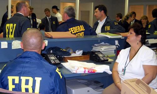 FBI personnel at work in arrest processing facility   Photo Credit: Rich Kolko, FBI