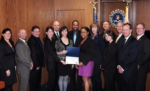 """Members of the FBI San Francisco Field Office and """"Futures Without Violence"""" pose for a photo following the award presentation for the 2011 Director's Community Leadership Award by Special Agent in Charge Stephanie Douglas. From left to right: FBI Chief Division Counsel Brenda Atkinson, FBI Assistant Special Agent in Charge Jeffrey Harp, FBI Administrative Officer Joshua Perez, FBI Special Agent in Charge Stephanie Douglas, Acting Assistant Special Agent in Charge John Bennett, Futures Without Violence Program Assistant Sarah Pritchard, Futures Without Violence Spokesman Brian O'Connor, Futures Without Violence Program Assistant Timmie Roach, Futures Without Violence Director of Communication Marsha Robertson, FBI Assistant Special Agent in Charge Joel Moss, FBI Community Outreach Specialist Alicia Sensibaugh, FBI Assistant Special Agent in Charge Michael Gavin, FBI Supervisory Special Agent Kevin Sherburne, FBI Assistant Special Agent in Charge Robert McMenomy."""