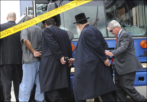 FBI agents in Newark lead arrested suspects in the corruption probe onto a bus.