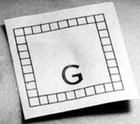 Close-up photograph of the paper scale shown in Figure 1, which features a capital letter G and a square frame composed of many smaller squares.