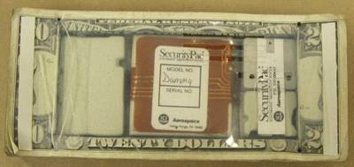 Figure 1 is a bank security dye pack. The stack of bills contains an electronic device disguised within a hollowed portion of the stack.