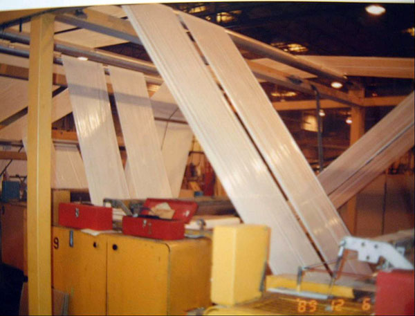 Figure 3: A photograph of a series of rollers flattening the plastic into long sheets and transporting it through the manufacturing process