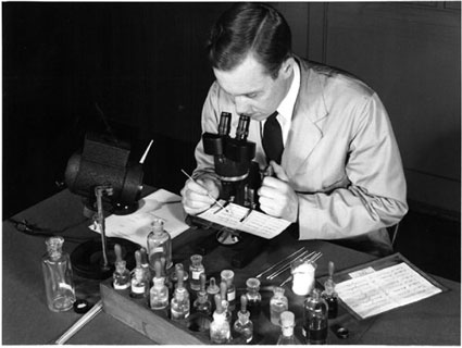A historical photo of a Laboratory technician examining ink on questioned documents