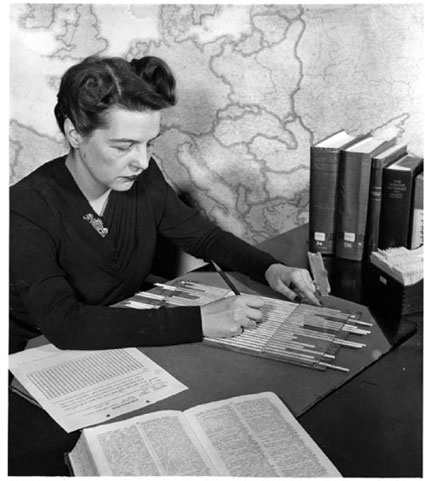 A historical photo of an examiner in the Cryptanalysis Section using alphabet strips to solve a clandestine cipher message