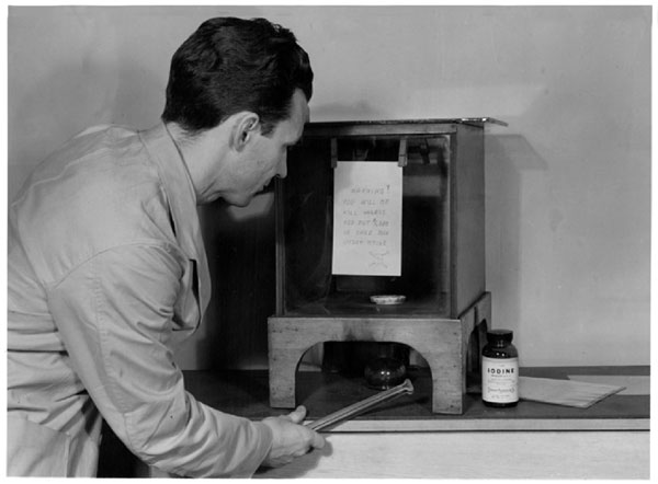 A historical photo of a Laboratory technician using iodine fumes to develop latent fingerprints on an extortion note
