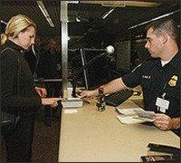 A  CBP officer takes a passenger's fingerprint scan to compare with the IAFIS database.