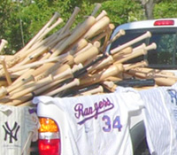 Bed of pickup truck filled with baseball bats and jerseys
