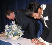 FBI OPA executive Cassandra Chandler and NCAAA President Jerry Fogel sign the Memorandum of Understanding