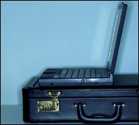 Open laptop sitting on briefcase