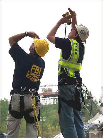 FBI ERT member and NTSB official survey the damage