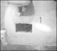 """View of ventilation grate through which prisoners gained access to utility corridor behind Cell Block """"B""""."""