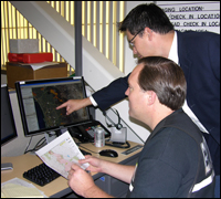FBI computer scientist Teddy Lindsey (standing) shows his geo-location tool to a member of the Sheriffs' department