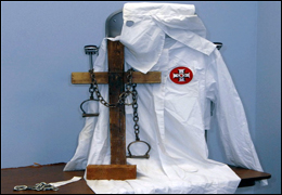 A few of the items in the Traveling Trunk, including a KKK robe, a charred cross, shackles, and a brick.