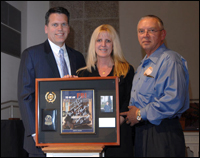 Tampa Special Agent in Charge Steven Ibison (left) presenting a framed memento to the parents of Mark Desmarais