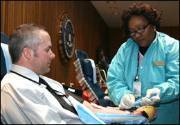 An FBI employee, with the help of a Bethesda Naval Center staffer, taking part in a military blood drive at our Washington headquarters.