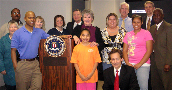 Carlie Shockey (front row, middle), along with her sister and mom (second row, second and third from right), during her recent visit with some of the Kansas City employees who worked on her kidnapping case 10 years ago. Also shown is Kansas City Special Agent in Charge Monte Strait (back row, center).