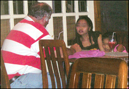 A Western man negotiating for a young Thai girl (far right), who clutches the arm of her trafficker. After settling on a price, the man left with the girl, and the trafficker left with her payment. Photo courtesy of the U.S. State Department.