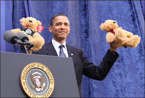 The President shows the crowd two FBI teddy bears for his daughters Sasha and Malia given to him by Director Mueller.