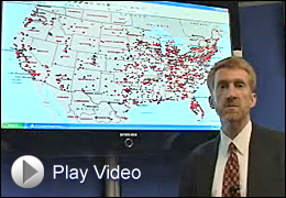 Special Agent Charles Pavelites in Front of Map with Video Play Button