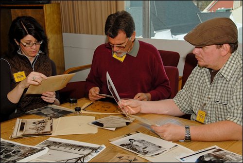 Tom Kaye (center), Carol Abraczinskas, and Brian Ingram examine archival photographs