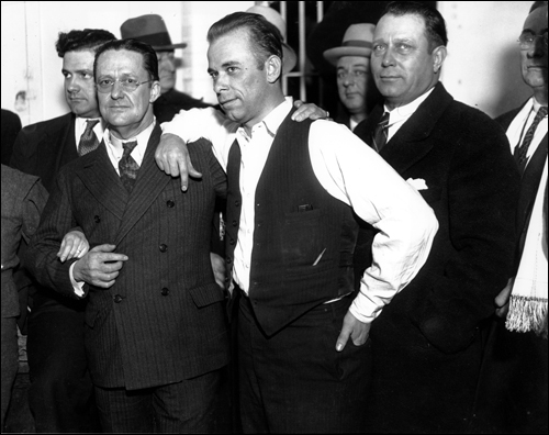 This photograph and similar ones taken that day helped lead to the firing of Lake County prosecutor Robert Estill (to Dillinger's left) and the sheriff (not pictured, but her arm is holding Estill's).
