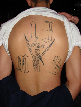 An MS-13 member arrested in the Houston salon robbery and extortion plot displays the gang affiliation tattooed on his back.