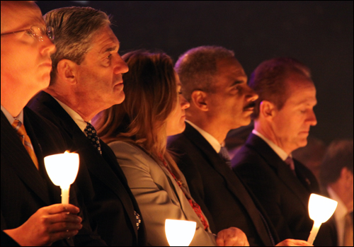 FBI Director Robert Mueller, COPS president Jennifer Thacker, and Attorney General Eric Holder, among others, holding candles in memory of the fallen officers