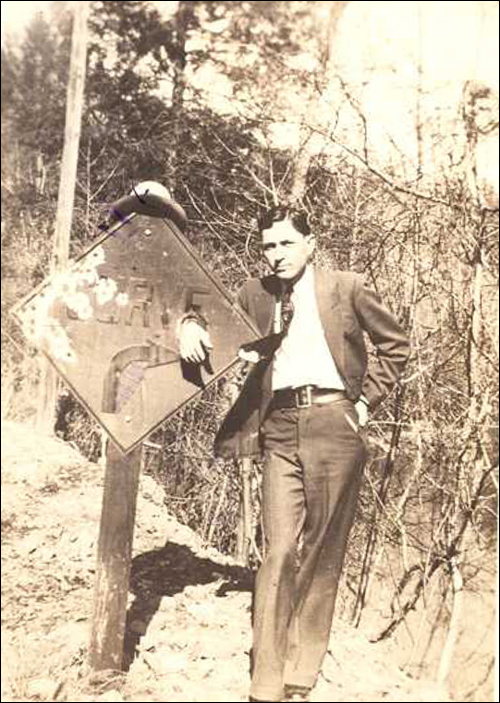 Clyde Barrow poses by a road sign