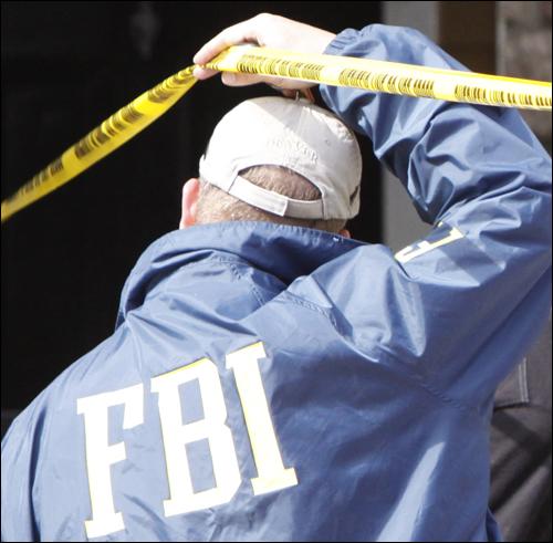 An FBI agent outside the apartment of Najibullah Zazi in Aurora, Colorado. AP Photo