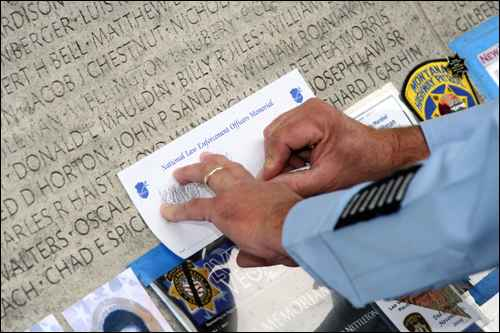 A visiting police officer makes a tracing of a fallen colleague's name. The Law Enforcement Officers Memorial now contains the names 18,983 officers from all 50 states, the District of Columbia, U.S. territories, and federal law enforcement and military police agencies.