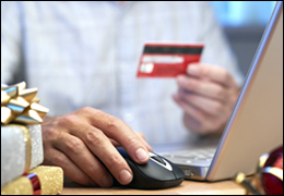 Man with Credit Card in Hand at Computer (Stock Image)